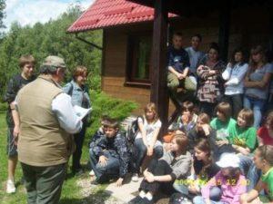 Młodzież szkolna z Prabut słucha z uwagą łowczego S. Mikołajkowa